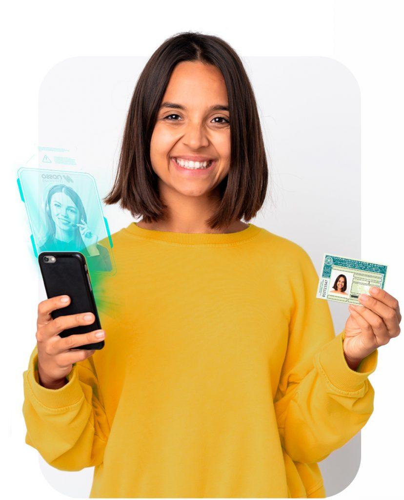 Mulher sorrindo enquanto segura seu celular em uma mão e seu RG em outra. No celular, uma montagem de um holograma de atendimento da Nosso Certificado.